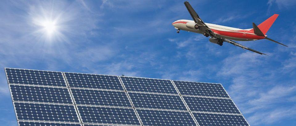 Plane soars over solar panel. (Shutterstock/wang song)