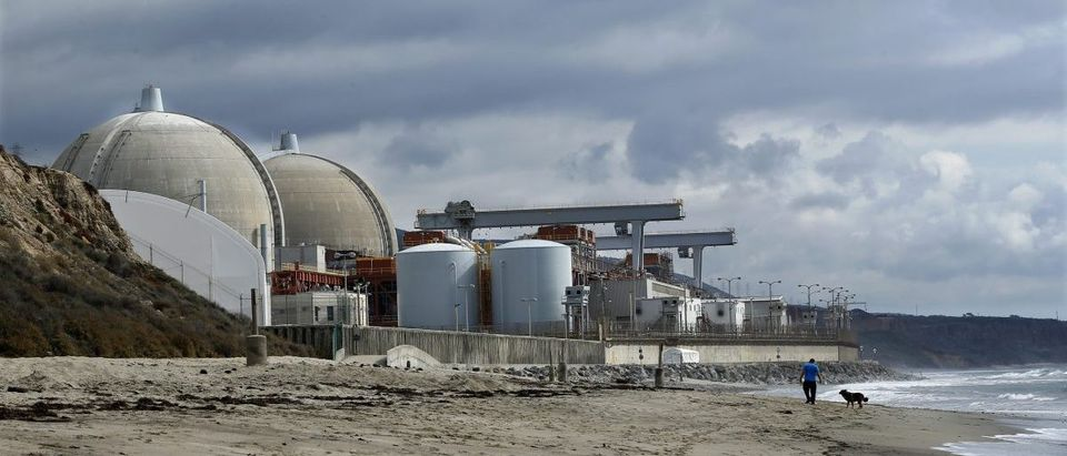 A man walks his dog next to damaged San Onofre power plant located next to San Onofre State Park in California