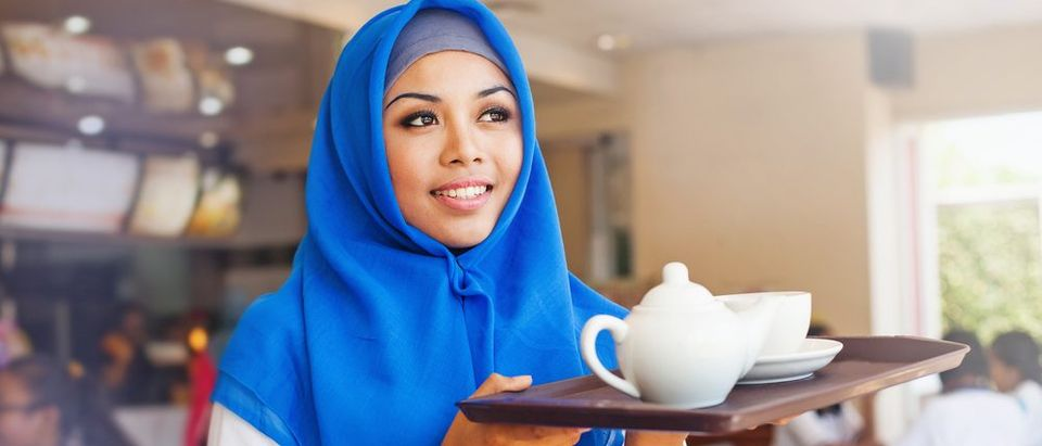 Muslim woman carries a tray of tea (Shutterstock)