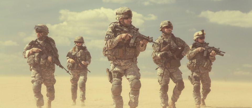 Soldiers walk through the desert