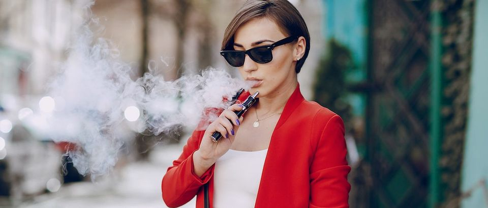 A young woman is smoking an e-cigarette. (Credit: Shutterstock/Oleg Baliuk)