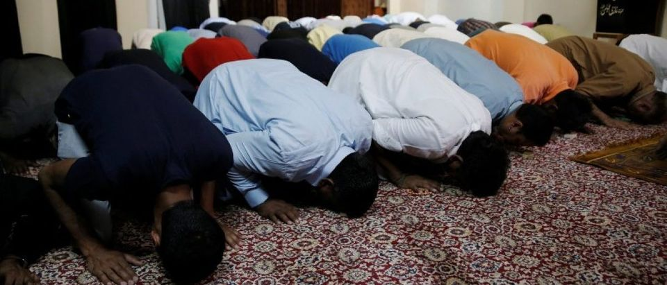 Muslim men attend Eid al-Fitr prayers at a makeshift mosque in a basement to mark the end of the holy month of Ramadan, in Piraeus