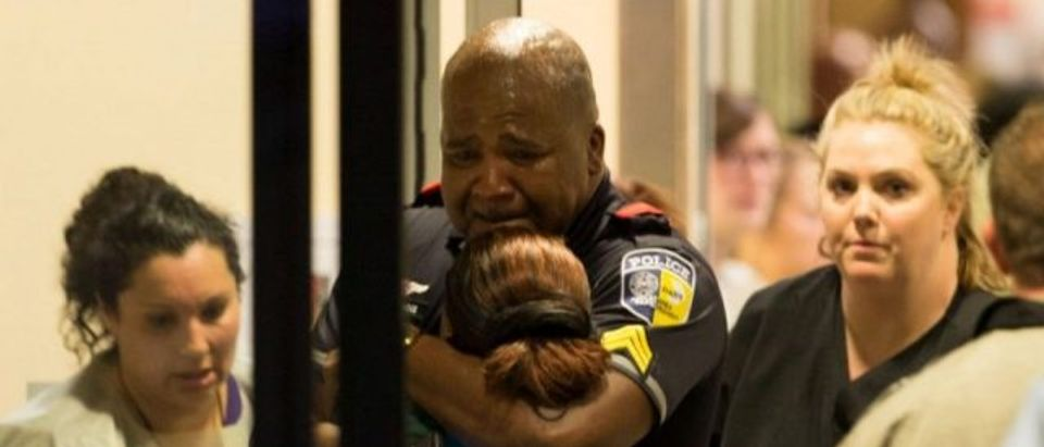 A DART police officer receives comfort at Baylor University Hospital emergency room entrance after a shooting attack in Dallas