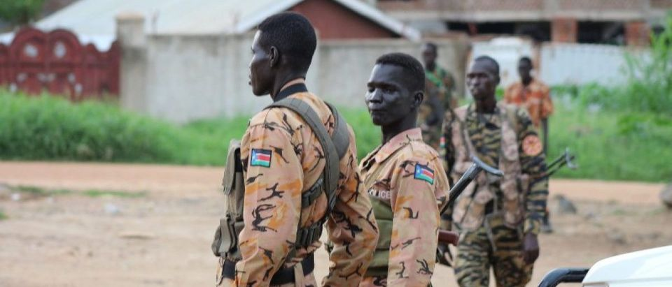 South Sudanese policemen and soldiers stand guard along a street following renewed fighting in South Sudan's capital Juba
