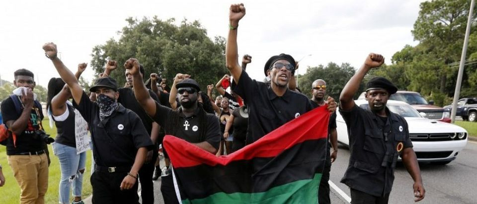 Demonstrators, wearing the insignia of the New Black Panthers Party, protest the shooting death of Alton Sterling near the headquarters of the Baton Rouge Police Department in Baton Rouge, Louisiana, U.S. July 9, 2016. REUTERS/Jonathan Bachman
