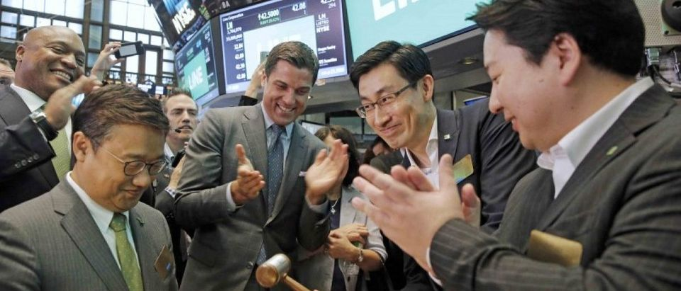 Japan's Line Corp. Chief Global Officer Jungho Shin rings the bell as CFO In Joon Hwang and Chief Strategy and Marketing Officer Jun Masuda look on along with NYSE president Tom Farley during the company's IPO on the floor of the New York Stock Exchange