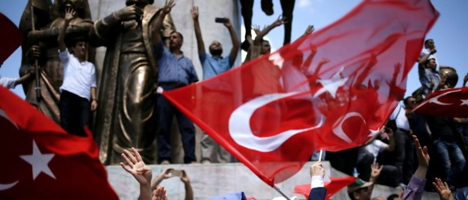 Supporters of Turkish President Tayyip Erdogan shout slogans and wave Turkish national flags during a pro-government demonstration in Sarachane park in Istanbul