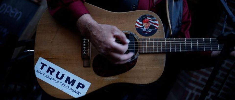 A man supporting Donald Trump plays a guitar near the site of the Republican National Convention in Cleveland, Ohio
