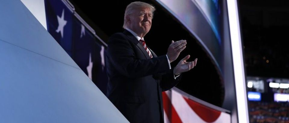 Republican presidential nominee Donald Trump applauds onstage as his running-mate Indiana Governor Mike Pence concludes his speech during the third night of the Republican National Convention in Cleveland, Ohio, July 20, 2016