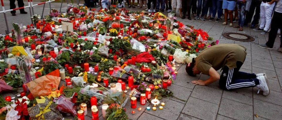 A man prays beside flowers laid in front of the Olympia shopping mall, where yesterday's shooting rampage started, in Munich