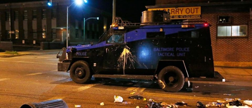 A police armored car is pelted with garbage as it moves down a street as clouds of smoke and crowd control agents rise shortly after the deadline for a city-wide curfew passed in Baltimore. REUTERS/Shannon Stapleton