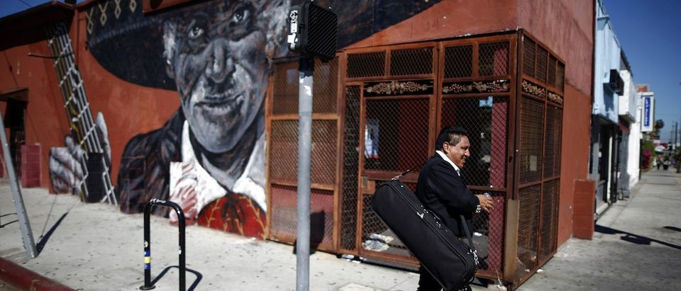 Mariachi musician walks past a mural in the Boyle Heights area of Los Angeles, home to many Mexican migrants, in California