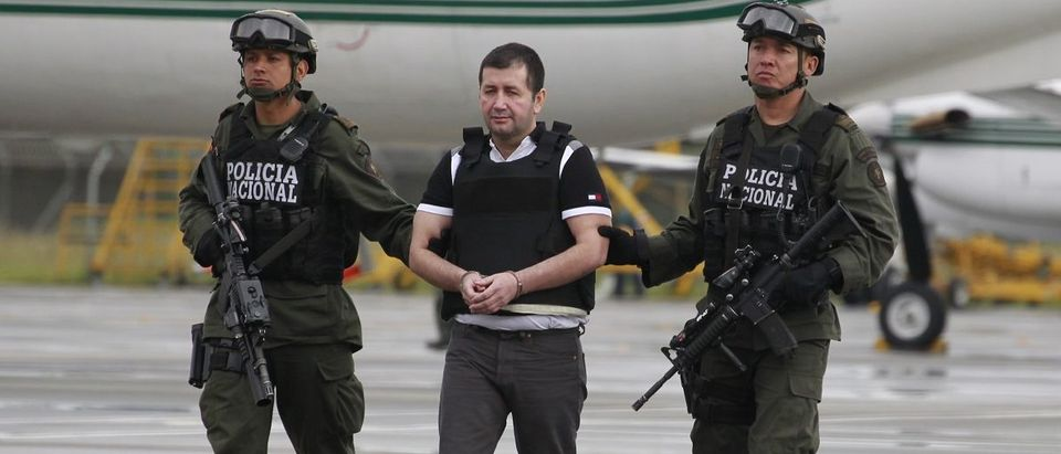 Police escort Colombian drug trafficker Daniel 'El Loco' Barrera as he is brought before the media, before being extradited to the U.S., at an airport in an anti-narcotics base in Bogota