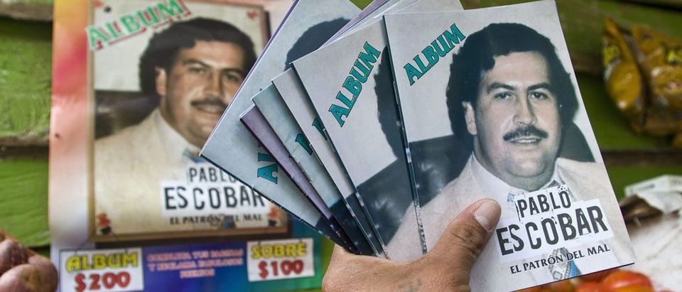 Woman shows an album of late drug lord Escobar which is sold in stores in Medellin