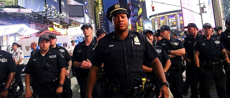 Police watch activists protest in Times Square in response to the recent fatal shootings of two black men by police (Getty Images)