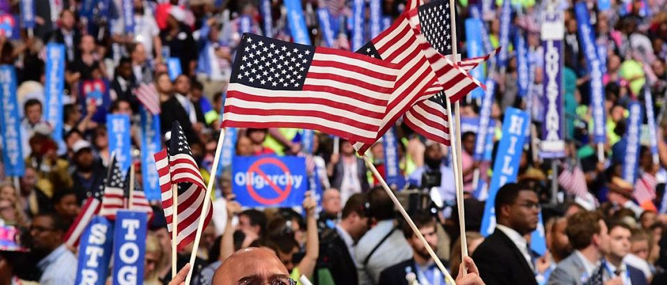 A man waves flags as Democratic presidential nominee Hillary Clinton addresses delegates on the fourth and final night of the Democratic National Convention at Wells Fargo Center on July 28, 2016 in Philadelphia, Pennsylvania. / AFP / Robyn BECK (Photo credit should read ROBYN BECK/AFP/Getty Images)