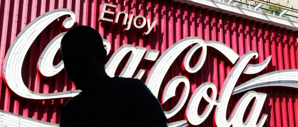 Pedestrian passes large Coca-Cola sign in eastern Sydney.