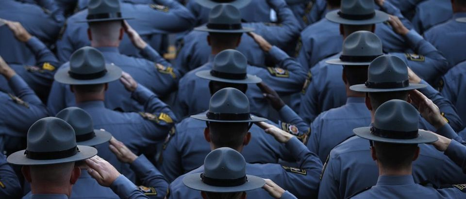 Pennsylvania State Police salute as they line the streets outside St. Peters' Cathedral in Scranton, as the casket carrying slain Pennsylvania State Police Trooper Corporal Bryon Dickson is carried into the Cathedral for his funeral service