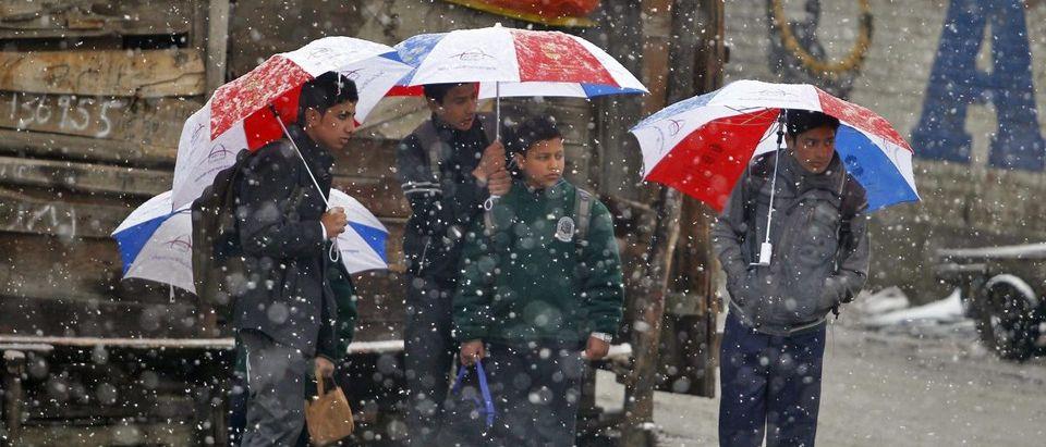 Schoolboys standing under umbrellas wait for a bus as snow falls in Srinagar