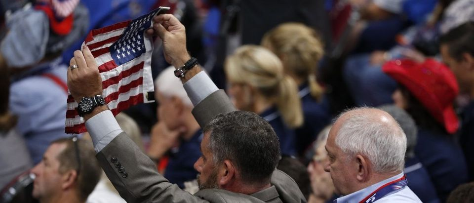A delegate is assisted as he holds the American flag at the Republican National Convention in Cleveland