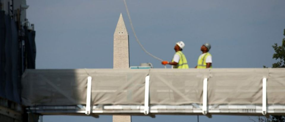 The Washington Monument looms in the background as construction workers look up toward the dome of the U.S. Capitol in Washington