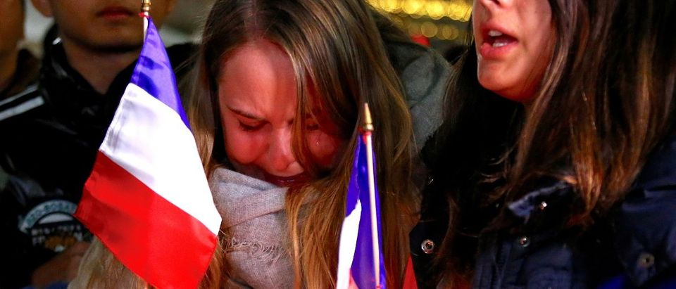 Members of the Australian French community cry as they sing the French national anthem during a vigil in central Sydney