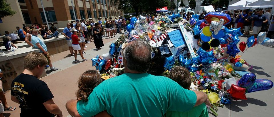 People hug at at a makeshift memorial at police headquarters following the multiple police shootings in Dallas, Texas, U.S., July 10, 2016. REUTERS/Carlo Allegri