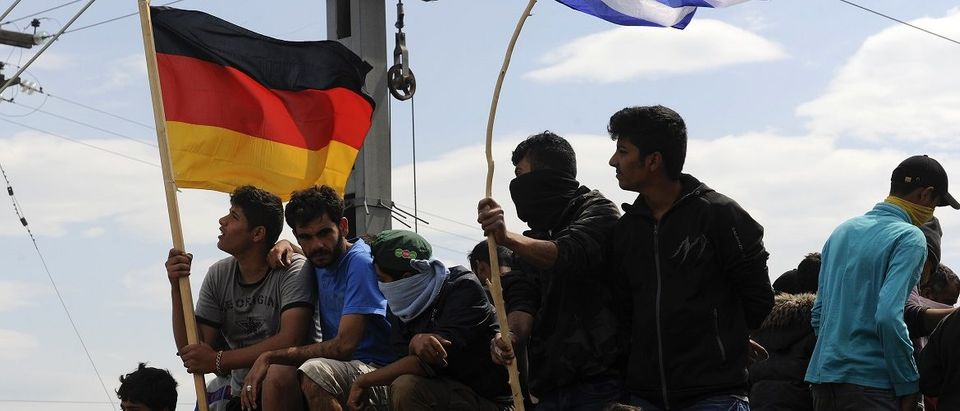Migrants and refugees hold German and Greek flags as they sit on top of a train carriage at a makeshift camp at the Greek-Macedonian border near the village of Idomeni