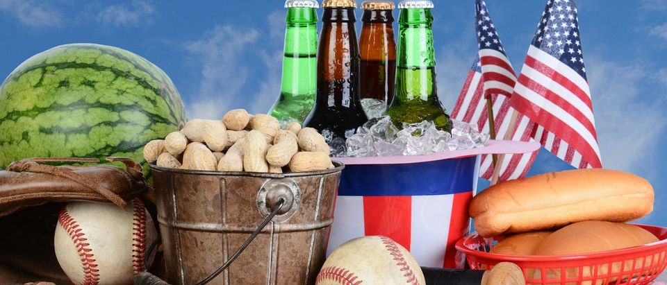 Picnic table ready for a Fourth of July celebration. Cold beer in an Uncle Sam Hat, watermelon peanuts, baseball, and hot dog buns fill the table, with a blue cloudy sky background. (Shutterstock)