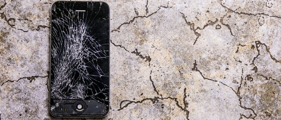 Mobile device fell on the floor and cracked iPhone screen. [Shutterstock - Rokas Tenys]