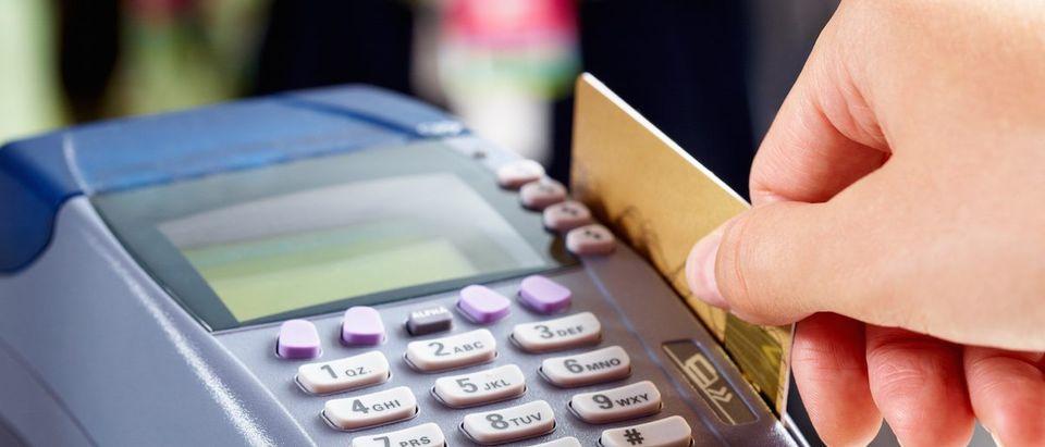 Customer Swipes Debit Card At A Convenience Store
