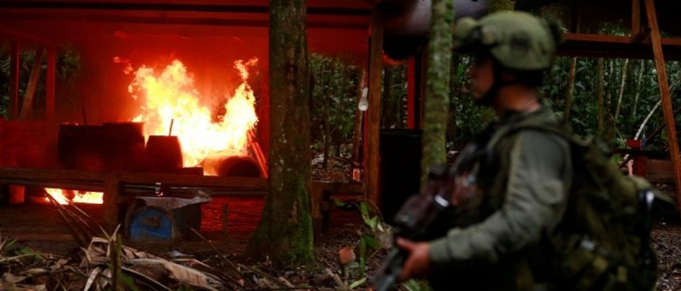 A Colombian anti-narcotics policeman stands guard after burning a cocaine lab, which police said belongs to criminal gangs, in a rural area of Calamar in Guaviare state, Colombia