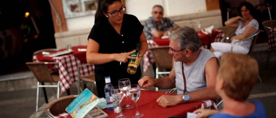 """A waitress serves wine to customers at the terrace of the """"Casino de Ronda"""" restaurant in downtown Ronda restaurant in downtown Ronda, near Malaga, southern Spain July 24, 2014. REUTERS/Jon Nazca"""