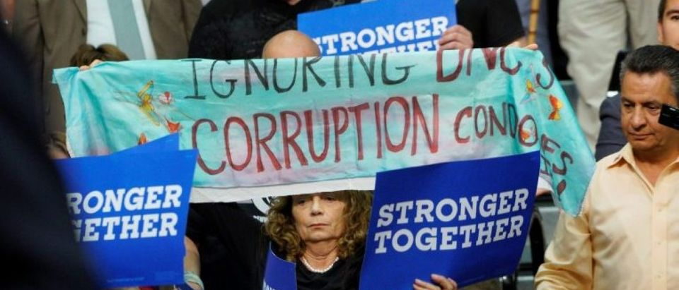 A protestor holds up a sign referring to DNC corruption at a rally for U.S. Democratic presidential nominee Hillary Clinton in Commerce City