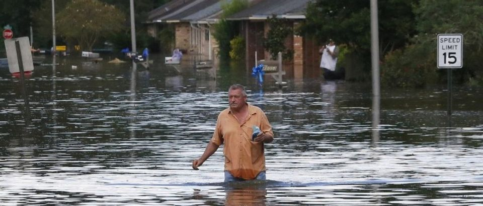 A man wades through a flooded street in Ascension Parish, Louisiana, U.S., August 15, 2016. REUTERS/Jonathan Bachman