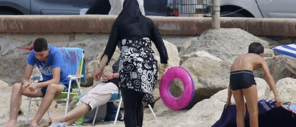 A Muslim woman wears a burkini, a swimsuit that leaves only the face, hands and feet exposed, on a beach in Marseille