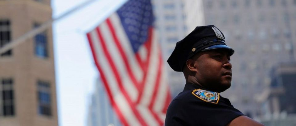 A New York Police Department officer stands on 5th Avenue in New York