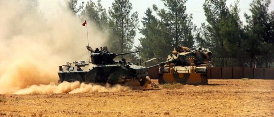 A Turkish army tank and an armoured vehicle are stationed near the Turkish-Syrian border in Karkamis in the southeastern Gaziantep province