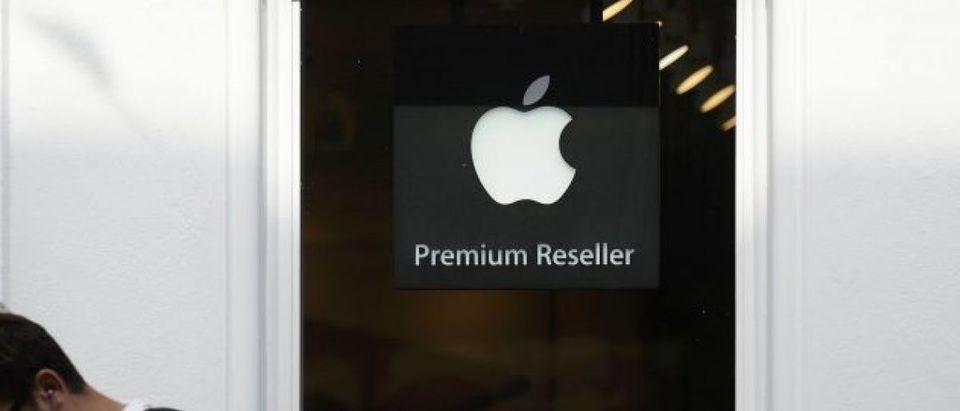 A man looks at his phone as he walks past an authorised apple reseller store in Galway