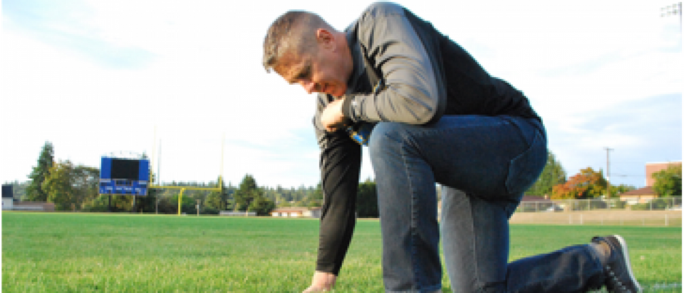 Coach Kennedy kneeling at the fifty-yard line on the Bremerton High School football field
