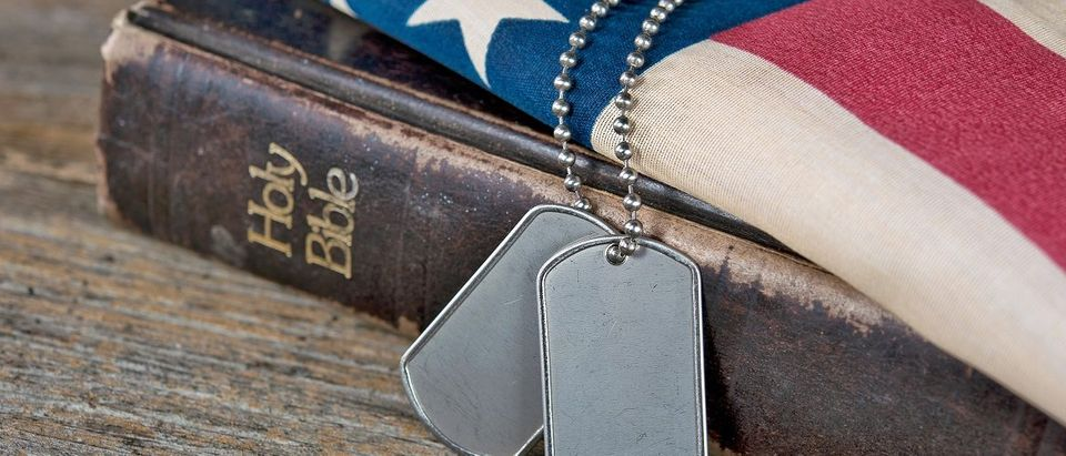 Bible displayed with an American flag and military dog tags. Shutterstock/Maria Dryfhout.