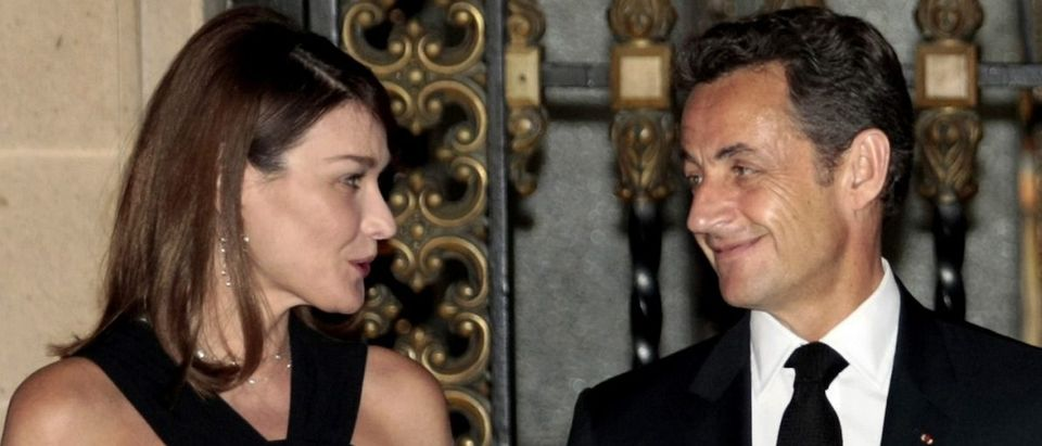 France's President Nicolas Sarkozy smiles with his wife First Lady Carla Bruni-Sarkozy after arriving to attend a dinner at the National Palace in Mexico City