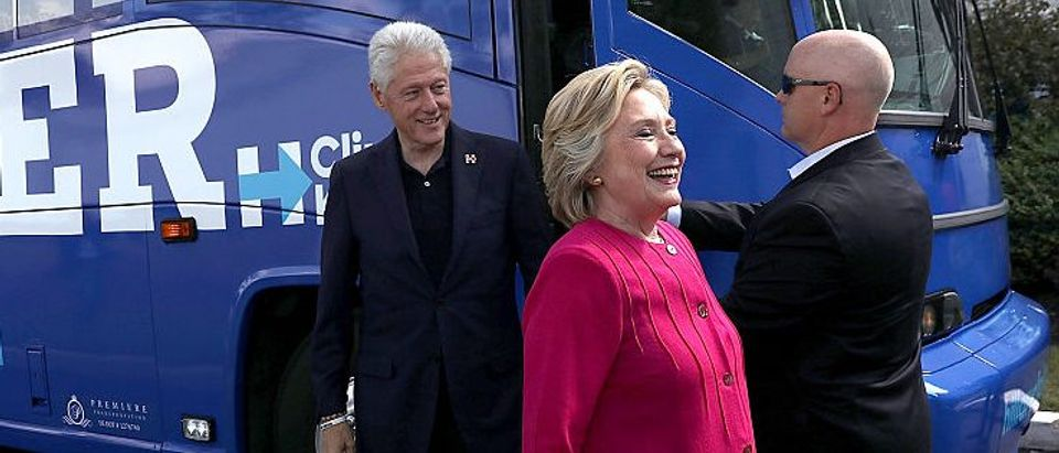 Hillary Clinton and her husband former U.S. President Bill Clinton walk off of their campaign bus before a rally in Hatfield, Pennsylvania (Getty Images)