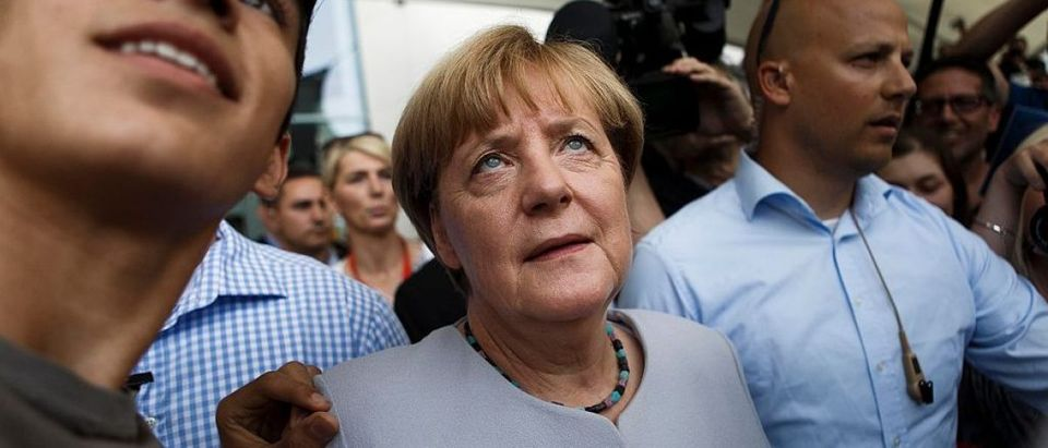 A visitor takes a selfie with German Chancellor Angela Merkel during the annual open-house day on August 28, 2016 in Berlin, Germany (Getty Images)