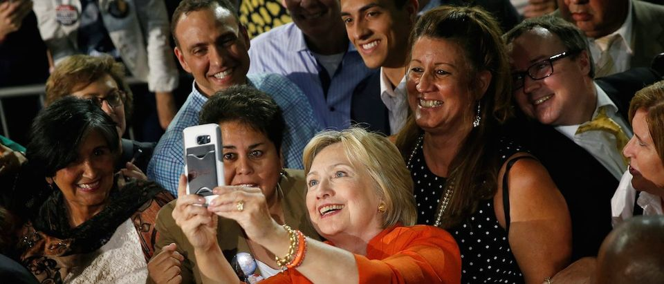 Democratic presidential nominee Hillary Clinton takes a selfie with supporters during a campaign rally in Kissimmee, Florida