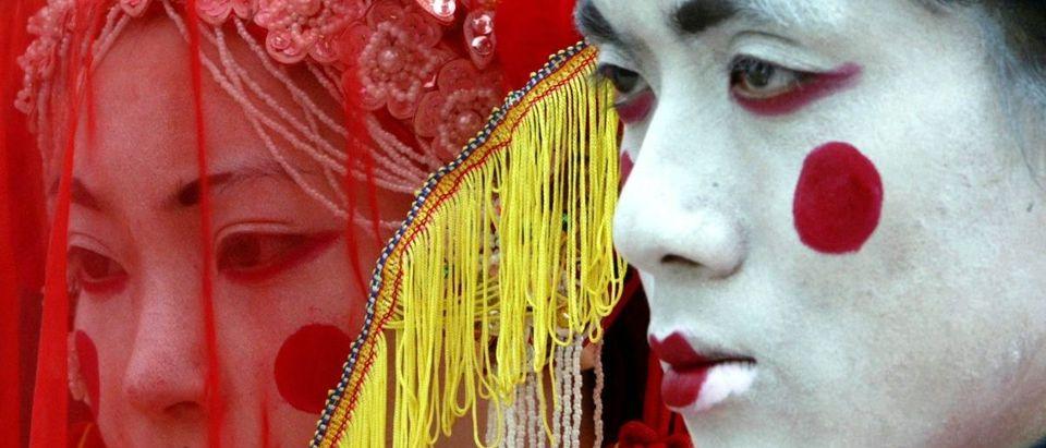 ARTISTS DRESSED AS CHINESE GHOST BRIDE AND BRIDEGROOM AT HONG KONGOCEAN PARK.