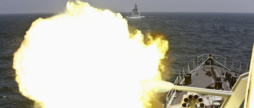 A Chinese navy vessel fires its cannon during the Joint Sea-2014 naval drill outside Shanghai on the East China Sea