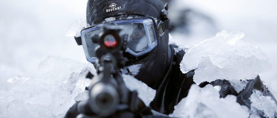 A member of the South Korean Special Warfare Forces takes his position in frozen waters during a winter exercise in Pyeongchang