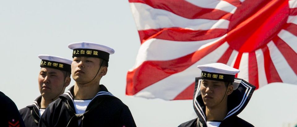 Soldiers of Japan's Maritime Self Defense Force stand in front of the country's naval ensign during the handing-over ceremony of the Izumo warship at the Japan United Marine shipyard in Yokohama