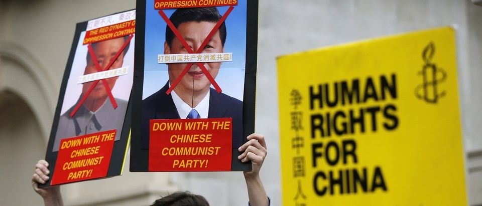 Human rights protesters hold up placards as they wait for China's President Xi Jinping to pass on the Mall during his ceremonial welcome, in London, Britain